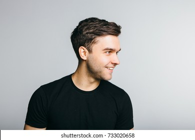 Casual guy with a warm smile over white grey background.