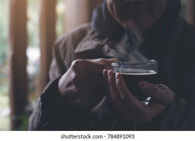 Casual handsome asian man drinking hot black coffee, americano with steam in coffee shop with morning light in winter, vintage tone, close up