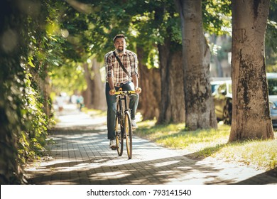 Casual handsome businessman going to work by bicycle.
