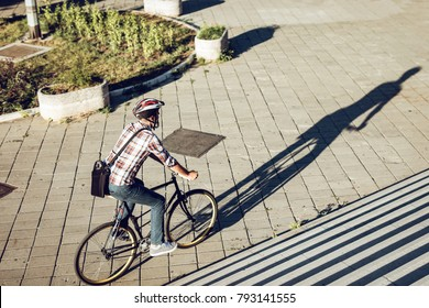 Casual handsome businessman with a helmet going to work by bicycle.