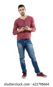Casual handsome stylish man holding mobile phone looking at camera.  Full body length portrait isolated over white background.