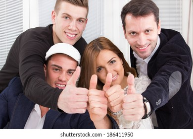 casual happy group of successful people make the ok thumbs up sign. Friendship and business concept with gesture of approval and success