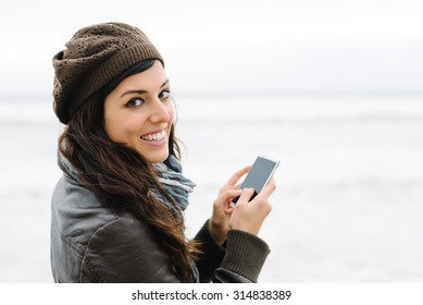 Casual happy woman texting message or email on smartphone outside. Female brunette using cellphone for internet browsing.