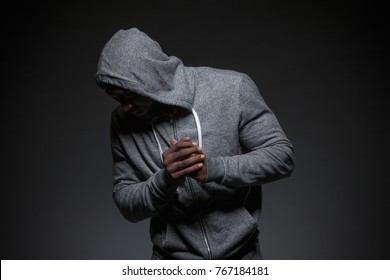 Casual image of African American male wearing a grey hoodie, photographed in studio.