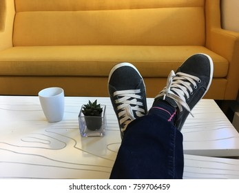 Casual interior scene. Feet up on a table with a yellow sofa in the background. Tennis shoes and jeans.