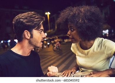 Casual interracial couple having an argument in a terrace