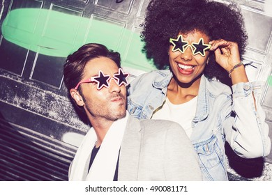 Casual interracial couple posing on graffiti background in glasses in the shape of stars