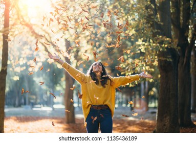 Casual joyful woman having fun throwing leaves in autumn at city park.