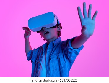 Casual kid in VR goggles experiencing another reality in neon lights on purple background