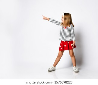 casual little girl in a red skirt pointing and looking to her side with a smile. isolated on white background