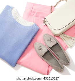 Casual look, blue jersey, pink pants, beige clutch and grey suede shoes, isolated on white background