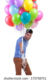 casual man behind a bunch of balloons is looking away to his side on white background