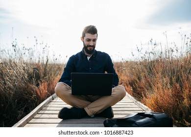 Casual man browsing laptop while lounging in beautiful fresh nature sitting on walkway in fields.