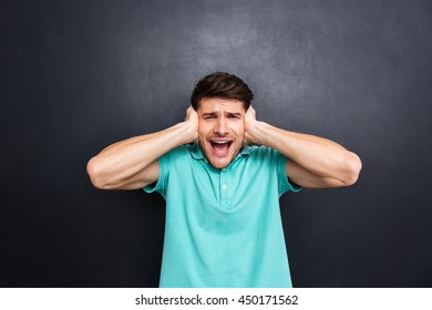 Casual man covering his ears and shouting isolated over black chalkboard