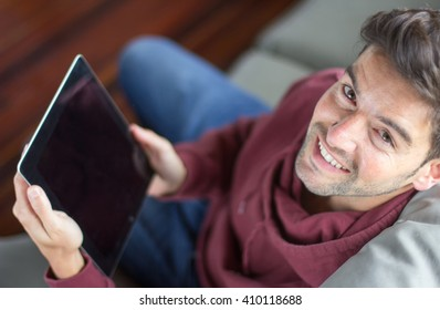 Casual man dressed with maroon sweatshirt holding his tablet and looking at the camera