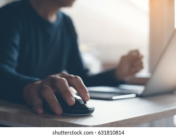 Casual man, freelance working on laptop computer and clicking wireless digital mouse with digital tablet on office table, close up, dark tone