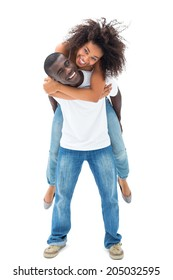 Casual man giving his smiling girlfriend a piggy back on white background