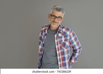 Casual man with grey hair standing on background, isolated