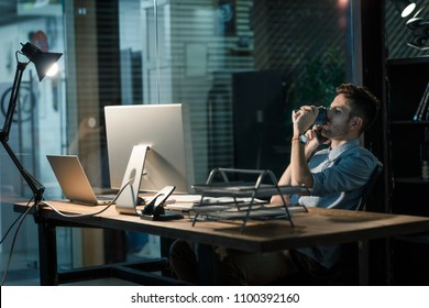 Casual man having phone call late in office while drinking energizing coffee at table.