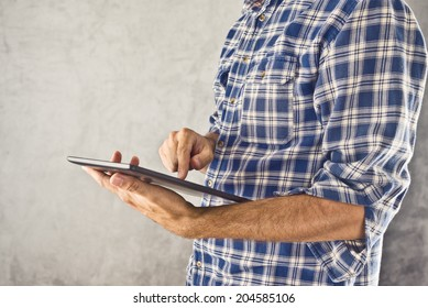Casual man holding 10 inch display digital tablet computer and using it for internet browsing, e-book reading and other multimedial experience.