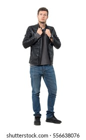 Casual man in jeans and leather jacket adjusting collar. Full body length portrait isolated over white background.