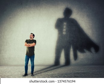 Casual man, keeps arms crossed smiling confident, casting a superhero with cape shadow on the wall. Ambition and business success concept. Leadership hero power, motivation and inner strength symbol.