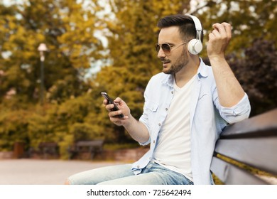 Casual man listening music and typing message in the park