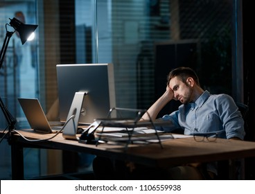 Casual man looking fatigue while working with computer in dark office alone.