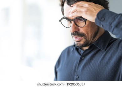 Casual man looking surprised reading bills to pay. Taxes, bank statement and loan debt. Male portrait bunkrupt with worried face and hand on his head