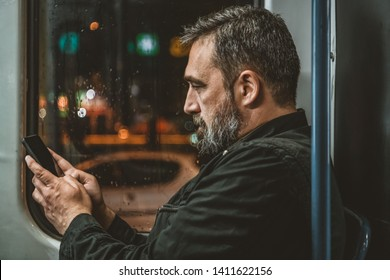 Casual man reading from mobile phone screen while traveling on metro. Wireless internet on public transport concept. Handsome hipster modern man traveling by tram in night.