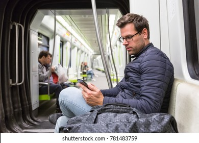 Casual man reading from mobile phone screen while traveling on metro. Wireless internet on public transport concept.