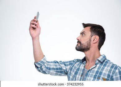 Casual man searching connection on the phone or making selfie photo on smartphone isolated on a white background
