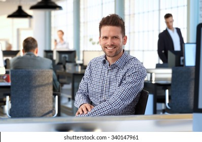 Casual man at sitting at desk in office smiling.
