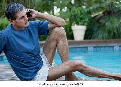 Casual man sitting near poolside talking on cell phone