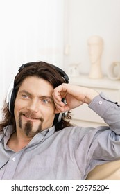 Casual man sitting on couch at home and listening music with headphones, smiling.