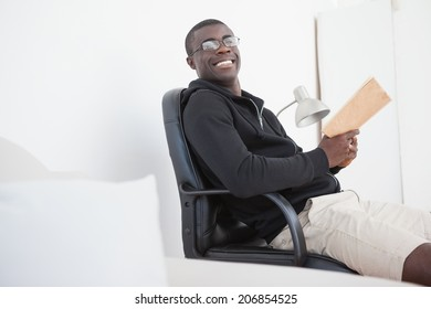 Casual man sitting on swivel chair reading a book at home in the living room