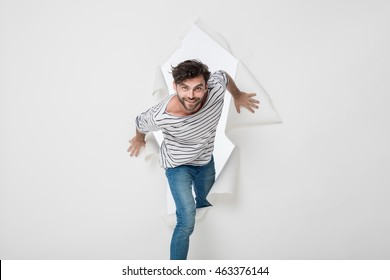 casual man in stripes and jeans breaking the paper wall, pasing from side to side