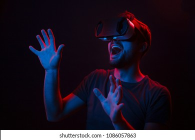 Casual man using glasses of virtual reality and exploring another world with great excitement in neon dark lights.