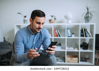Casual man using phone in modern bright living room.