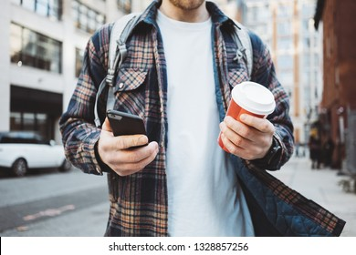 Casual man walking on the urban street sidewalk with cup of hot coffee and texting on mobile phone. Close-up