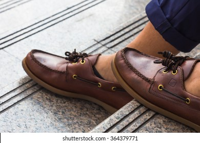 Casual man wear brown leather shoes sitting at staircase in the afternoon.