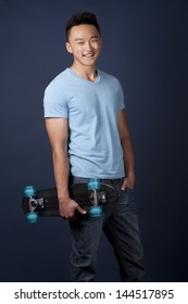 casual man wearing blue tshirt and jeans holding skateboard