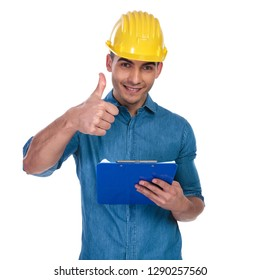 casual man wearing safety helmet makes thumbs up sign and holds papers while standing on white background, portrait picture