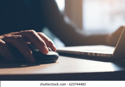 Casual man working on laptop computer and clicking wireless digital mouse, close up, dark tone
