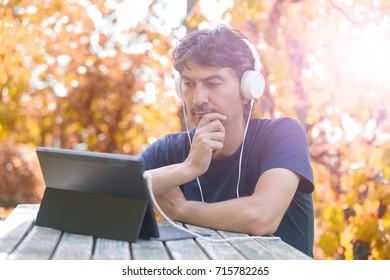 casual man working with a tablet pc, with headphones, outdoor