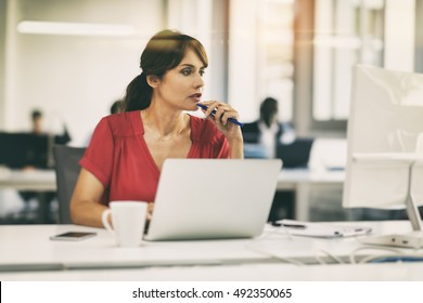 Casual mature businesswoman focused on computer screen in coworking office startup