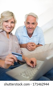 Casual mature couple doing online shopping through computer and credit card at home