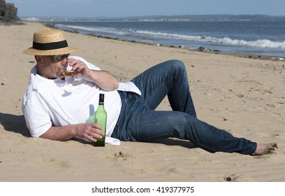 Casual mature man relaxing on the beach with a bottle of wine.