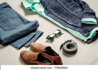 casual men fashion set: jacket, shirt, jeans, belt, shoes sweater on a gray background