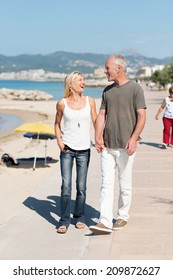 Casual middle-aged couple walking at the coast strolling along a waterfront promenade hand in hand chatting as they go